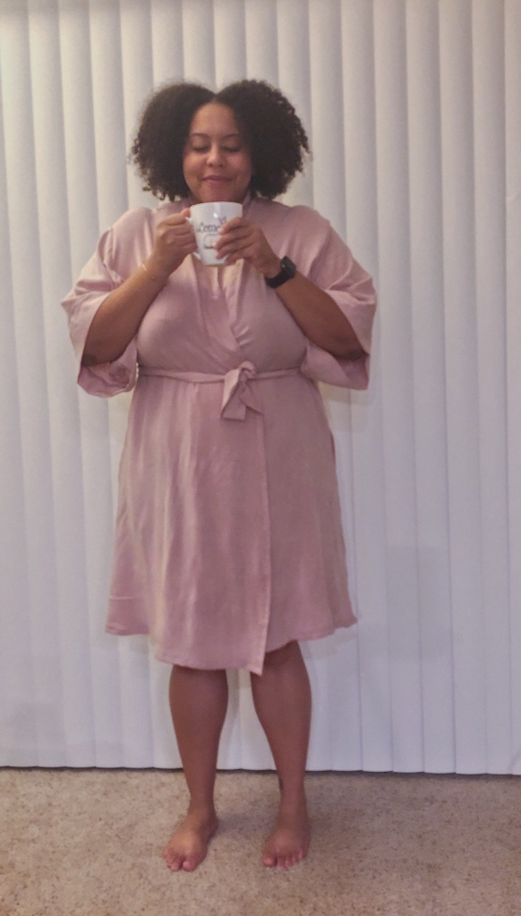 Sierra is wearing a light rose kimono and holding a coffee cup